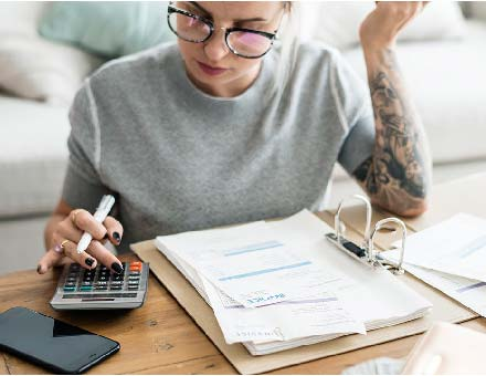 A young woman uses a calculator with business papers.