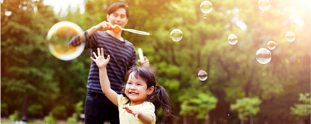 Father and daughter play with bubbles.