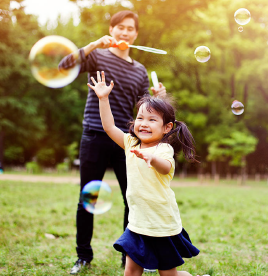 A FATHER AND DAUGHTER PLAY WITH BUBBLES.